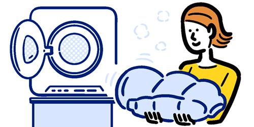 乾燥機で乾かしたダウンジャケットを持つ女性