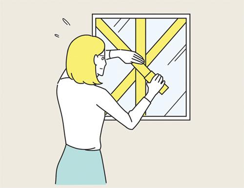 窓を補強する女性のイラスト